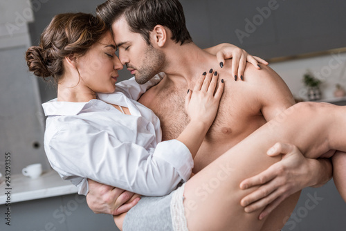 passionate shirtless man holding in arms attractive girlfriend