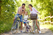 Leinwandbild Motiv family, leisure and technology concept - happy mother, father and little daughter with smartphone and bicycles in summer park