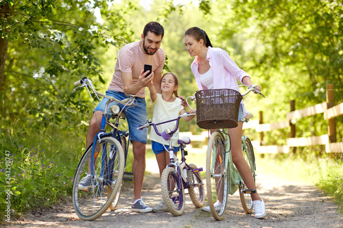 family, leisure and technology concept - happy mother, father and little daughter with smartphone and bicycles in summer park