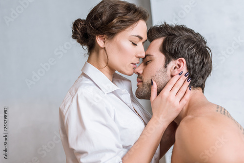 adult woman kissing man with passion and closed eyes