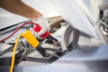 Car Mechanic Man Using Battery Jumper Cables To Charge A Dead Battery..Close Up Hand Charging Car Battery With Electricity Red And Yellow Jumper Cables. Car Repair Service Concept.