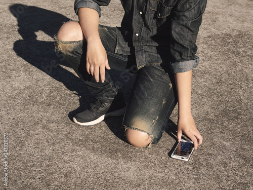 Young man picking broken and cracked screen smartphon from