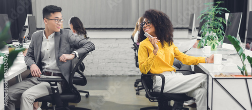 Foto  multiracial young business people smiling each other while working together in o