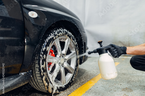 Fotografiet  Carwash, cleaning the wheels with a special agent