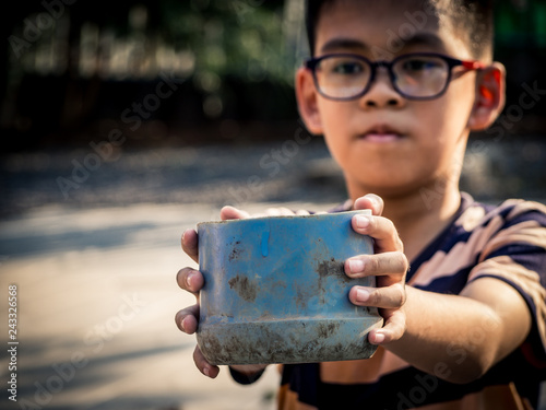 Fényképezés  Child homeless holding plastic bowl with hungry and need food from traveler on street at the city
