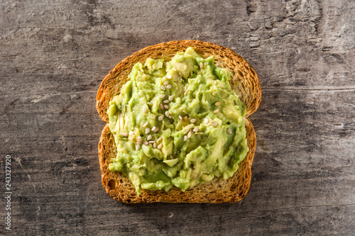 Toasted breads with avocado and sesame seeds on wooden table. Top view