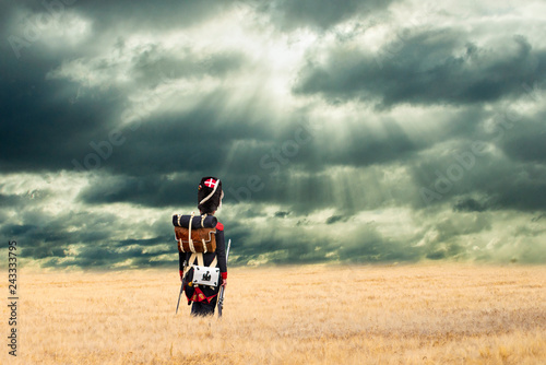 Fotografia French grenadier watching napoleonic soldiers walking into countryside with stormy clouds