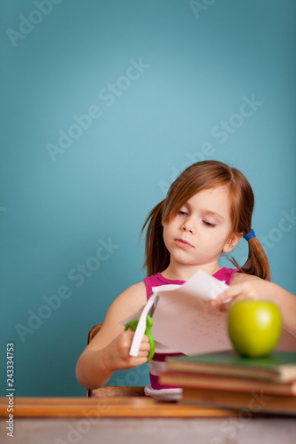 Fotografie, Obraz  Girl in School Desk Cutting Paper Craft - Room for Text
