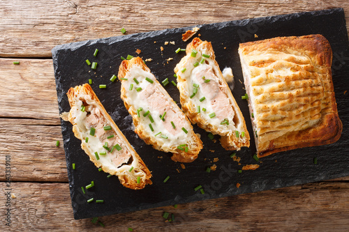 Sliced puff pastry pie stuffed with salmon and cheese close-up. horizontal top view