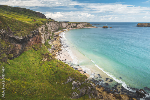 White sand beach of the Northern Ireland shoreline. Green grass covered cliff washed by the turquoise transparent sea water. Beauty of wild untouched environment. Breathtaking Irish landscape.