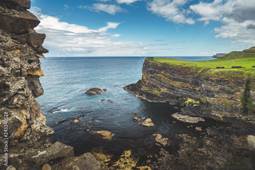Irish bay surrounded by the green covered rocks. Northern Ireland. Amazing scene the water surface next to the Irish land. Blue cloudy sky background. Beauty of wild virgin nature. Stunning landscape.
