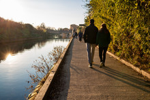 Lovers  Walking In The Park Along A River At Sunset