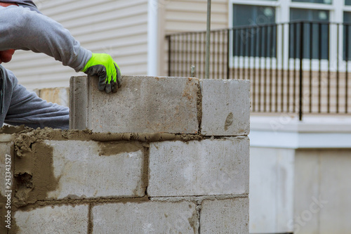 Fotografie, Obraz masonry worker make concrete wall by cement block and plaster at construction si