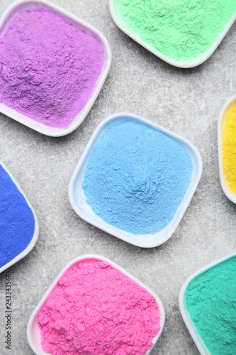Fotografia  Colorful holi powder in bowls on grey background