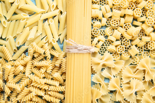 Foto  Different uncooked pasta on blue wooden table