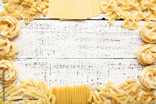Fotografía  Different uncooked pasta on white wooden table
