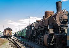 Old Rusty Steam Locomotive Beside A Railway Station Platform. Retro Train.