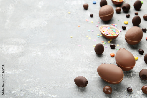 Fotografía  Chocolate easter eggs with colorful candies on grey wooden table