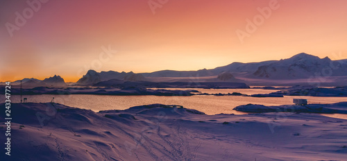 Poster Antarctica Antarctica sunset panoramic view. Epic bays surrounded by the snow covered land with the animal footprints. Breathtaking polar scenery. Ideal background for the winter collages and illustrations.