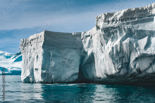 Fotobehang Antarctica Close-up sunlit iceberg. Antarctica scene in blue and white tints. Amazing snow covered block of ice with icicles floating among the polar ocean. The cloudy sky background. Picturesque winter scenery.