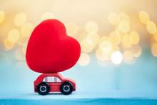 Miniature Red Car Carrying A Red Heart On Shine Bokeh Background.