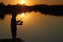 Silhouette Of Boy Fishing Off A Dock At Sunset.
