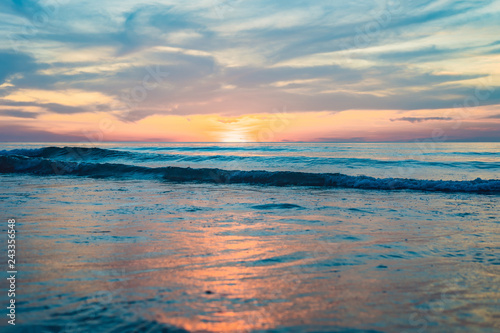 Door stickers Sunset gold sunset over beach with wave splashes in summer of Thailand