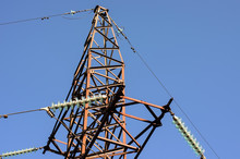 Upper Part Of Old Rusty High Voltage Electric Power Tower Against Blue Sky Background, Closeup