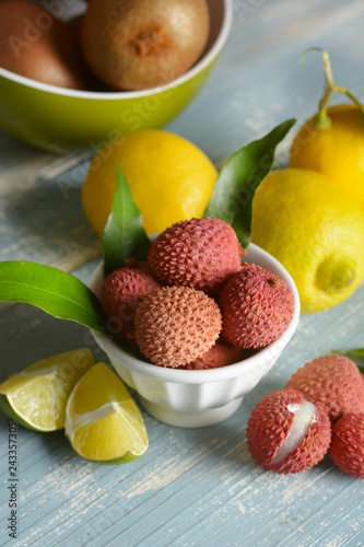 lychees fruits in the white bowl with citrus fruit around