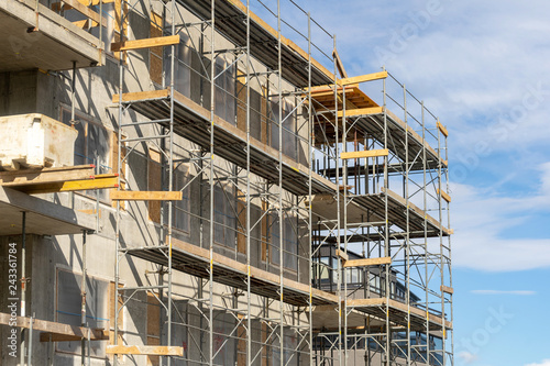 Fotografie, Obraz Photo of multistory high rise building with scaffolding