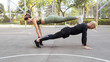 Couple working out on a sportsground, doing a straight-arm plank exercise