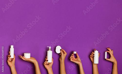 Leinwand Poster Female hands holding white cosmetics bottles - lotion, cream, serum on violet background