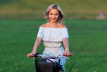 Soft Focus Photo. A Young, Beautiful Blond Woman With A White Bike In A Green Meadow.