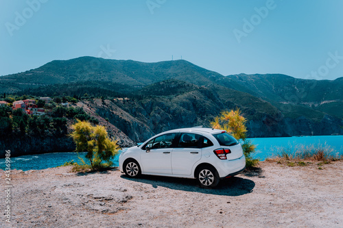 Vacation travel with car concept. Rental hired car in front of amazing bay with turquoise water. Discover Mediterranean Islands. Summer time holiday trip