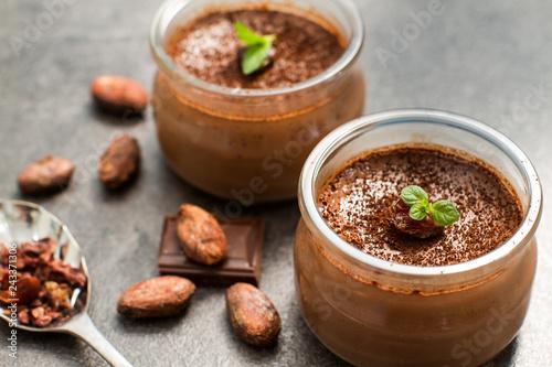 Foto op Plexiglas Dessert Chocolate dessert panna cotta in glass jars with raw cocoa beans
