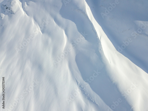 Fotografie, Obraz  Aerial view of snow covered terrain in mountain area