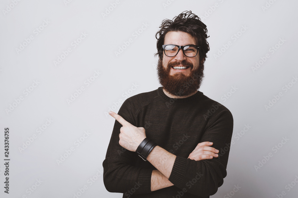 Fototapeta Stylish hipster model in glasses is pointing at  copy  space with crossed hands