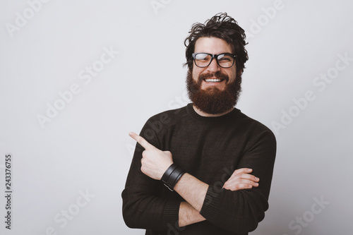 Fotografija  Stylish hipster model in glasses is pointing at  copy  space with crossed hands