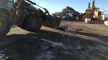 Bulldozer With Bucket Cleans Up Mess By Clearing A Path From Debris On Ground In Junkyard And Pushes It Into Pile While Another Machine Works In Background.