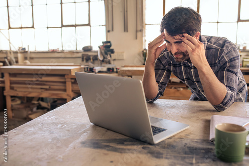 Fotografie, Obraz  Stressed out woodworker using a laptop in his carpentry studio