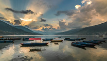 Boats Moored On Lake Against Cloudy Sky During Sunset