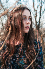 Thoughtful Woman Wearing Tiara While Standing Against Bare Trees In Forest