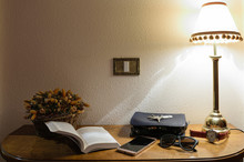 Various Objects With Illuminated Lamp On Wooden Table At Home