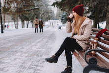 Woman Drinking Coffee While Sitting On Bench Against Trees At Park During Winter