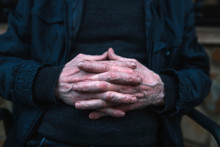Midsection Of Senior Man With Hands Clasped Sitting On Bench