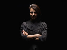 Portrait Of Confident Woman With Arms Crossed Standing Against Black Background