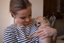 Smiling Woman Carrying Chihuahua At Home