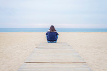 Rear View Of Woman Looking At Sea While Sitting On Boardwalk Against Sky