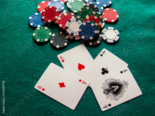 Fotografía  The four aces of a poker deck and poker chips of various colors on a green mat