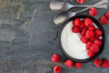 Bowl Of Yogurt With Raspberries. Top View, Side Border On A Dark Slate Background. Copy Space.